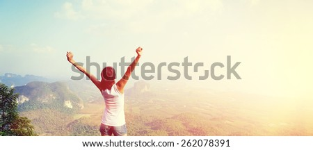young woman cheering open arms at mountain peak - stock photo