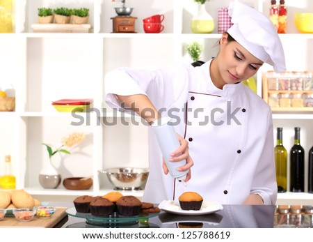 Young woman chef cooking cake in kitchen - stock photo