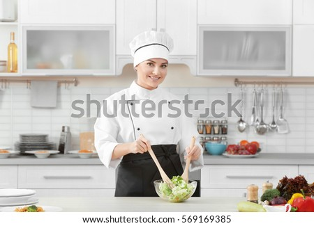 Young woman chef cooking salad in modern kitchen