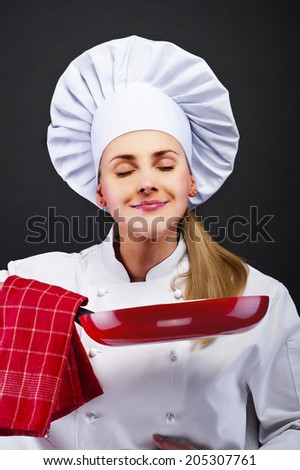 young woman chef with different tools on dark background  - stock photo