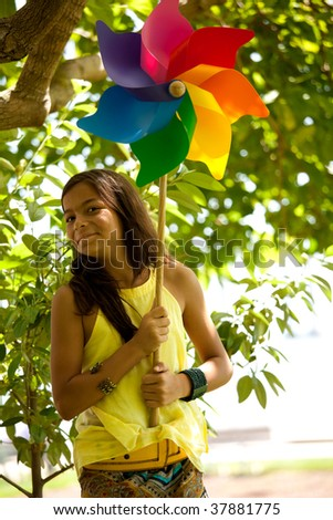 young woman child having fun at the park with her pinwheel