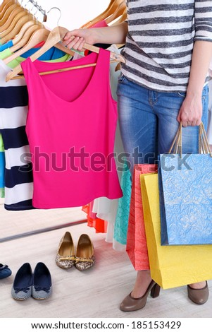 Young woman choose clothes near rack with hangers