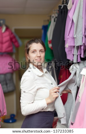 Young woman chooses casual wear at clothing store