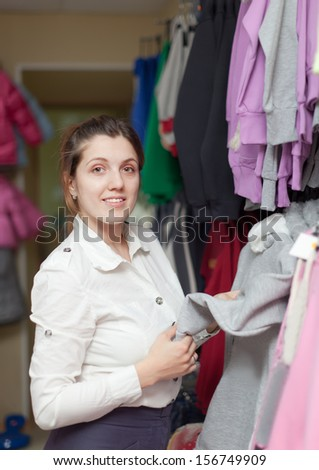Young woman  chooses clothes at clothing store