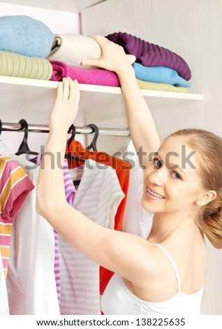 Young woman chooses clothes in the wardrobe closet at home - stock photo