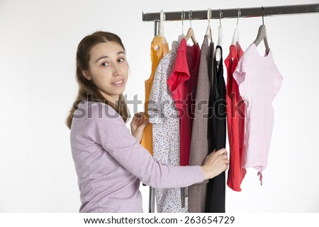 young woman chooses clothes on , isolated on coat rack white background