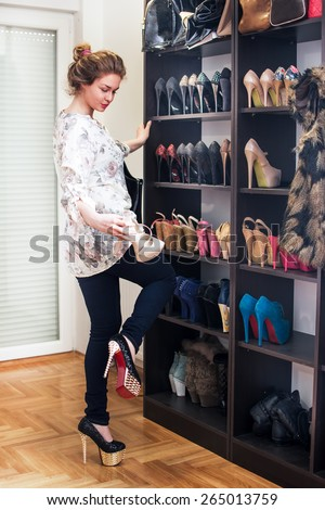 Young woman chooses shoes at shoe closet. - stock photo
