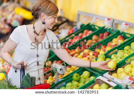 Young woman choosing apples in grocery store - stock photo