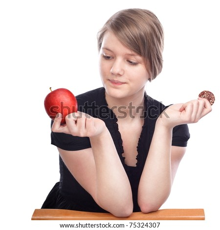 Young woman choosing between apple and chocolate cookies on white background