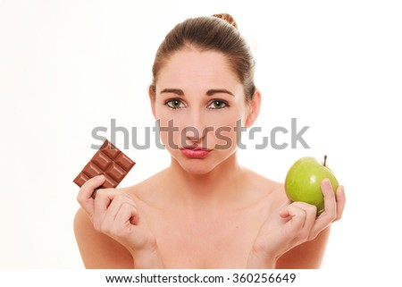 Young woman choosing between apple and chocolate isolated on a white background  - stock photo