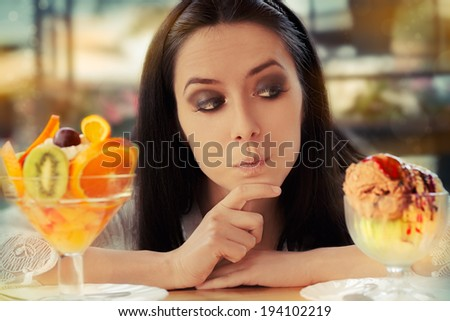 Young Woman Choosing Between Fruit Salad and Ice Cream Desserts - Beautiful woman has to choose between two desserts, fruit salad or ice cream  - stock photo