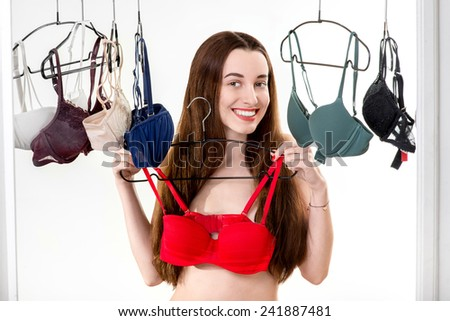 Young woman choosing bras to wear in the white wardrobe - stock photo
