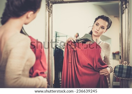 Young woman choosing clothes in a showroom  - stock photo