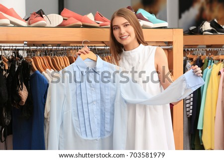 Young woman choosing clothes in mall