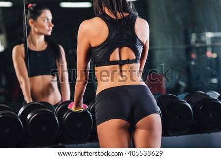 Young woman choosing dumbbells in gym - stock photo