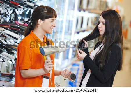 Young woman choosing electric hairdryer in home appliance shopping mall supermarket - stock photo