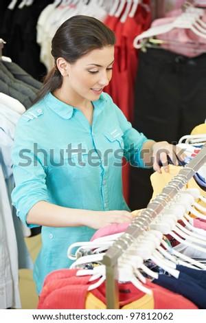 Young woman choosing garments during clothing shopping at apparel store - stock photo