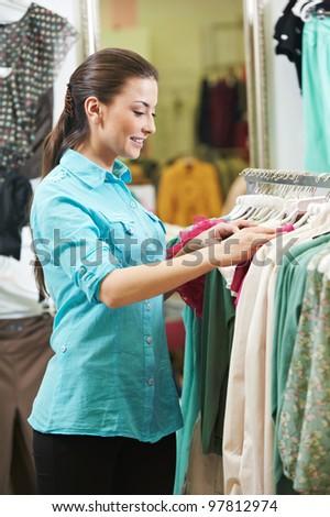 Young woman choosing garments during clothing shopping at store - stock photo