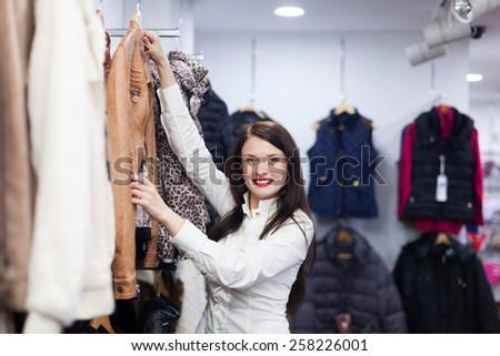 Young woman choosing jacket at clothing store - stock photo