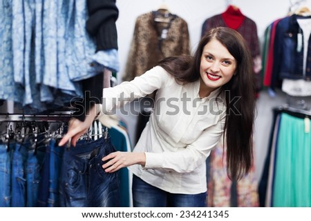 Young Woman choosing jeans at fashionable shop - stock photo
