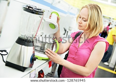 Young woman choosing kitchen mixer blender in home appliance shopping mall supermarket - stock photo
