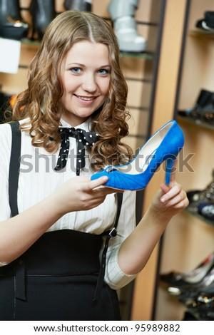 Young woman choosing shoes during footwear shopping at shoe shop - stock photo