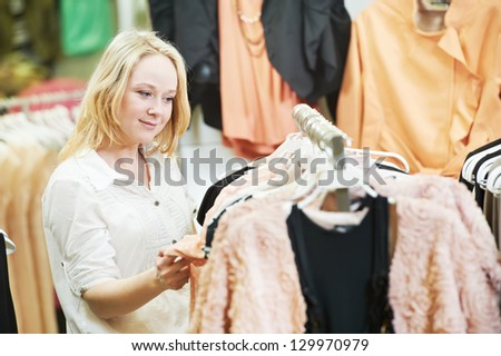 Young woman choosing sweater and blouse during clothing shopping at store - stock photo