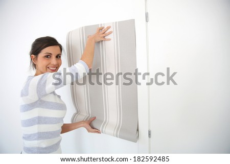 Young woman choosing wallpaper for new home - stock photo