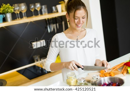Young woman chopping vegetables in the kitchen - stock photo