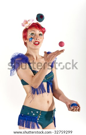 Young woman circus performer juggling balls in the air - stock photo