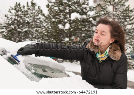 Young woman cleaning car windows from snow in winter season