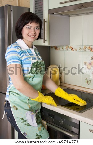 Young woman cleaning  cooker at the kitchen. Smiling female washing stove top. - stock photo