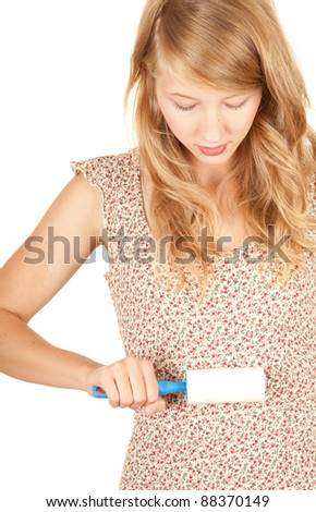 young woman cleaning dust with lint roller, white background - stock photo