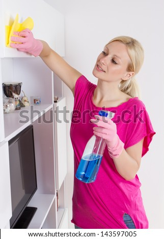 Young woman cleaning furniture at home.