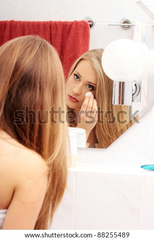 Young woman cleaning her face in the bathroom - stock photo