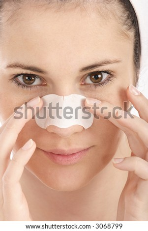 Young woman cleaning her skin with clear-up strip - stock photo