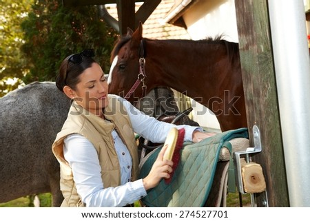 Young woman cleaning horse saddlery outdoors, brushing saddle-cloth. - stock photo