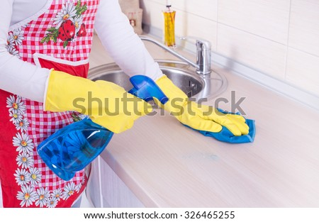 Young woman cleaning kitchen countertop with spraying detergent and rag - stock photo