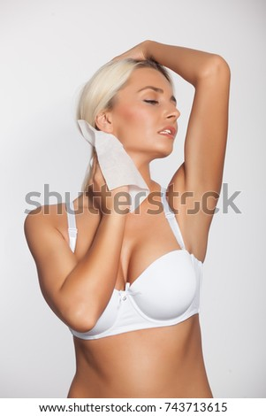 Young woman cleaning neck with wet wipes, body breast lingerie