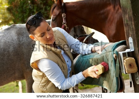 Young woman cleaning saddlery outdoors, brushing saddle-cloth.