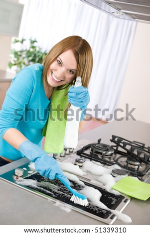 Young woman cleaning stove in modern kitchen with brush and glove - stock photo