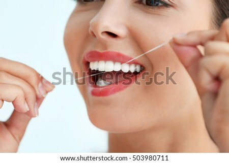 Young woman cleaning teeth with dental floss, close up