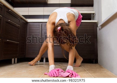 Young woman cleaning the kitchen floor at home - stock photo