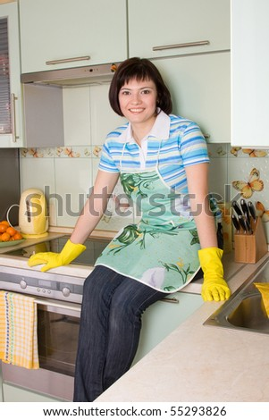 Young woman cleaning the kitchen. Smiling female is sitting on the stove top. - stock photo