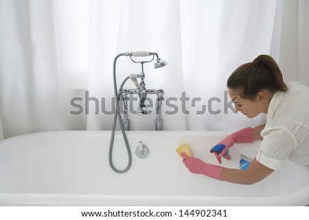 Young woman cleaning up the bathtub with sponge and cleaner at home - stock photo
