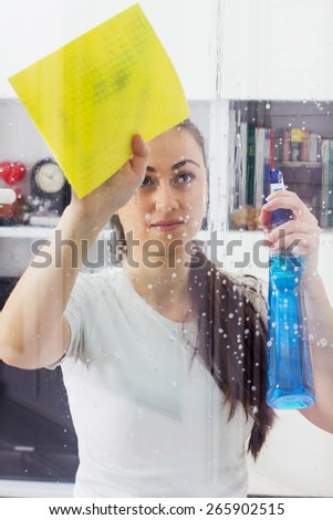 Young Woman Cleaning Windows Glass at the home.  - stock photo