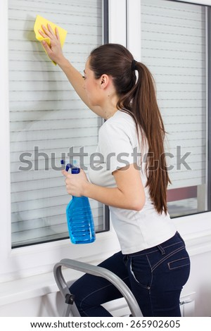 Young Woman Cleaning Windows Glass on ladder at the home.  - stock photo