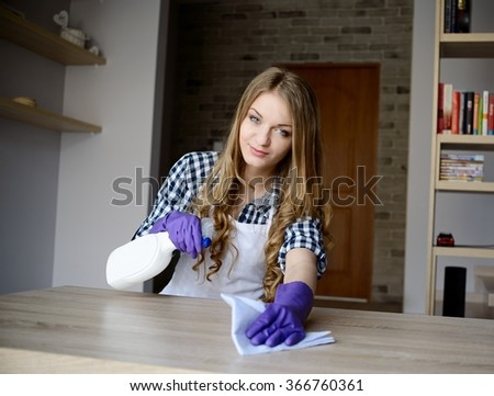 Young woman cleans a wooden table, uses rag and cleaning fluid in a spray. Dressed in a white apron and a plaid shirt. Protective rubber gloves on her hands - stock photo