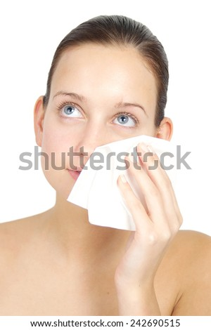 Young woman cleansing her face and applying lotion. Skincare concept.