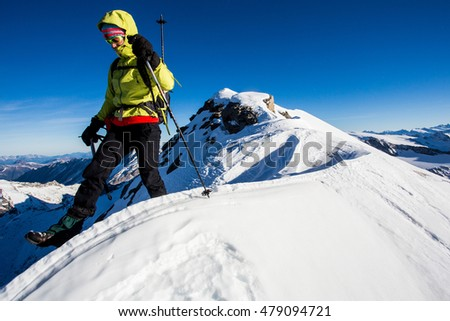 Young woman climbing challenging snow ridge in the Alps